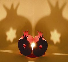 """The """"Star of David"""" Symbol on a tea-light holder in the shape of a pomegranate. When placing a lighten tea-light candle, you will see the beautiful lights as they appear on your walls! Laser-cut metal with high standard paint (powder coating). Back in stock: available in Bordeaux. Arrives with a tea-light candle. Gift wrapped."""