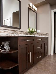The mix of classic dark wood, oversized modern brushed-nickel drawer and cabinet pulls, and granite countertops lends a timeless feel to this master bathroom. It offers plenty of storage for two people to stash clutter, keeping the room neat and tidy. Photography and design by Nip Tuck Remodeling
