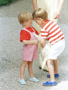Prince Harry & Prince William playing with a dog.