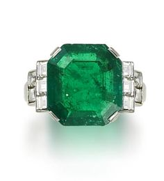 An emerald and diamond ring  The cut-cornered square-cut emerald, weighing 8.12 carats, between two rows of square-cut diamonds in collet settings, diamonds approximately 1.00 carat total. Art Deco or Art Deco style.