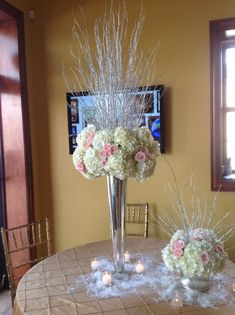 Wedding centerpiece of white hydrangea, pink spray roses and silver birch branches atop mercury glass riser. White hydrangea, pink spray roses and silver birch branches in glass cylinder surrounded by snow and votive candles. Doristhefloristt@aol.com