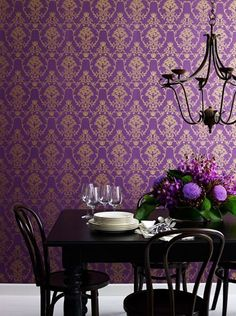 Love the combination of the ornate wallpaper and the wrought iron chandelier and simple table and chairs.