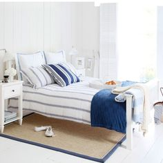 Create a nautical look  Simple blue and white stripes combined with white wood panelled walls and a sisal rug creates a classic coastal feel.