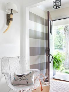 Stripes; horn sconce; white wire chair; bird cushion