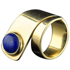 CARTIER Dinh Van Yellow gold & lapis lazuli ring  USA  circa 1965  18ct yellow gold ring of graduated wrap-around design with a single oval lapis lazuli cabochon in a collet setting. Dinh Van for Cartier New York, circa 1965.  http://jewelry.1stdibs.com/