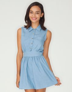 Shirt inspired chambray denim style Motel dress with button through front in a light pastel blue. Featuring short sleeves, cinched in diamond shape waist, cute circle style flippy skirt and button up front with cute collar detail. Perfect for summer in lightweight cotton this skater style dress looks great teamed with colour pop flatforms and a bare leg, dress up with a studded belt and tights for an evening look. Fabric Content: 85% Cotton, 15% Polyester - Model Wears: XS - Model Height…