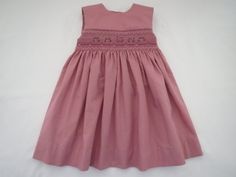 This little sleeveless sundress comes made of a beautiful 100% cotton deep rosy pink fabric and is hand smocked in lovely shades of light to dark rose and ivory. Bullion rose clusters with green leaves intermingled with tiny ivory pearls decorate the smocking across the front. The bodice is lined and all edges are finished with a fine french seam. The hem is sewn in with a hidden stitch and this entire little dress is made with utmost quality and care for details. The back fastens up with 3…