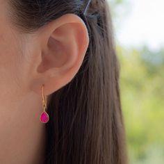 Preciosos pendientes de Plata de Ley con piedra rosa fucsia tallada en forma de lágrima, montados en bases de gancho con presiones de silicona.