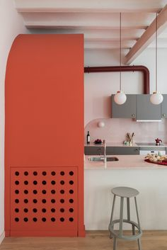 The living and dining area is dominated by a coral-coloured arched volume that conceals the guest toilet.