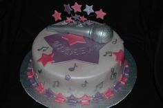 """Musical Star - I was asked by my client to create a cake for her daughter's 12th birthday. Her daughter is an aspiring singer, and wants to be a star when she grows up. She suggested the microphone and stars, and this is what I came up with.  9"""" chocolate, filled with ganache and chocolate buttercream. Cake first covered with ganache and then with fondant. Microphone is gumpaste painted with silver lustre dust, and the other decorations are fondant dusted with lustre and sprinkled with ..."""