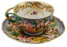 CAPODIMONTE PORCELAIN CHERUBS TEACUP & SAUCER - hand painted porcelain cup and saucer set molded in relief depicting exterior scenes with people and cherubs throughout cup and saucer