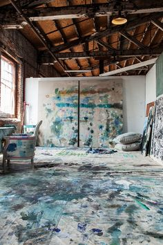 "Studio of Ballard Designs Exclusive Artist Kiki Fitzgerald   | Large paint-splattered tarps cover the floor of Kiki's studio. The pair of large paintings at the back are titled ""Rebel Rebel"" and measure 5'x8′, one of the artist's favorite sizes to paint. Photo Credit: Jimmy Johnston"