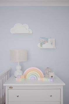 Serene nursery with pale blue skies and cloud accents like these book shelves.