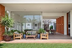 """Na varanda, estofados com estrutura de bambu da Decor Vime. """"Tecidos e objetos desenham um interior quente e confortável, que dialoga com as linhas contemporâneas da arquitetura"""", diz a arquiteta."""