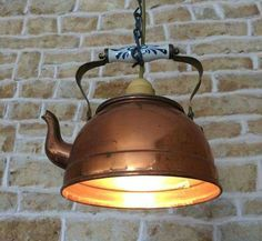 Copper tea pot with the bottom cut off and made into a pendant light.