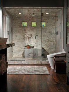 duchas modernas, ducha de obra separada con mampara de vidrio, baño con suelo de tarima, pared de piedra, tres pequeñas ventanas
