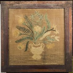 """Ann Hunsicker Needlework Theorem Vase of Flowers, depicting a large white vase of flowers and leaves sewn onto a linen ground with a saying along the bottom, signed lower right """"Ann Hunsicker"""", 17 3/4"""" square, custom framed under glass, although no provenance comes with this piece there have been other Barbara Hunsicker made samplers from the Shippack, Pa area in the early 19thC, we believe this could have been done by her sister which corresponds to when we believe this theorem was sewn…"""
