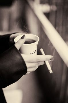 This image is also black and white with a brownish tone, however it has more of a pink hue to it and therefore is much lighter than the other two images. It also feels less like doom is eminent, and more like the choice of color palette as well as focus on only the person's hands, coffee, and cigarette are trying to tell us something about the person in the image and not the world around them.