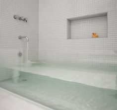 """Glass bathtub - need different tiles Flipping through the Summer 2011 issue Boston Home, I was struck by the beauty of this """"invisible"""" tub. Made from a thick sheet of glass inserted between the two tile walls. Boston-based architecture & design firm Stern McCafferty created this custom bath based on an inspiration photo from owners Amy and Ethan d'Abelmont Burnes. They gut renovated their South End rowhouse when they bought the property next door and decided to combine them."""