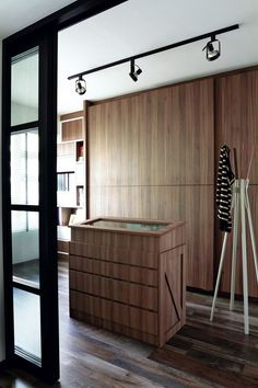 Natural wood grain finishes add warmth to the stark black and white loft concept of the interiors.