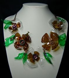 """My entry in to the Happy Mango Beads Trash to Treasure competition 2011. The flowers and leaves on my necklace are made from plastic drink bottles, cut & melted in to shape. It's further decorated with parts from a broken necklace that I bought from a thrift store, and pieces from a couple of broken watches...face, cogs, hands etc., hence Greenpunk...a nod to Steampunk, but Green."""" I was really pleased to win Grand Prize :o)   Greenpunk - Trash to Treasure by Goddess-Jewels, via Flickr"""