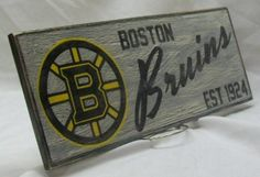 The Boston Bruins. This sign is hand painted on cabinet grade birch and measures 6 1/2  x 17 . This sign is hand painted with quality black,
