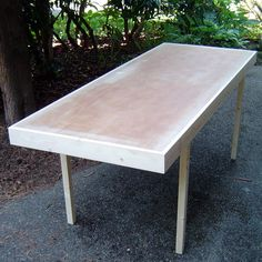 Upgrade a used hollow core interior door into a decent lightweight table, with the help of a couple of pieces of construction lumber. The 1 x 4's around the outside give it a finished look and stiffen the table considerably, and with the help of a couple of crosspieces, give the legs something to be attached to. Assuming you have a free door, the table will cost you less than $5, and will recycle something that is otherwise likely to be dumped.