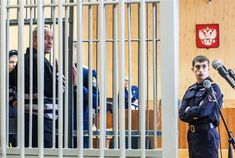 Mikhail Popkov stands inside a defendant's cage during a court hearing in Irkutsk