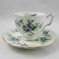 Gorgeous tea cup and saucer set made by Aynsley. Pretty blue roses all over the tea cup and saucer and on the inside rim of the tea cup. Gold trimming on cup and saucer edges, as well as on angular handle. Pattern is called Marine Rose  Excellent condition (see photos).  Markings read: