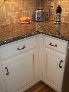 Antique White cabinet, black / oil rubbed bronze hardware, baltic brown granite counter top, and varying size tiled backsplash