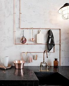 Exposed copper piping doubles as utensil storage in this urban chic kitchen.