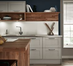 Contrasting worksurfaces give a contemporary twist to the classic shaker look. Take a look at Howdens for kitchen design ideas.