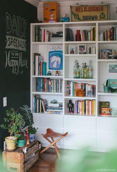 Estante clean para expor objetos garimpados, parede de lousa e mesinha feita com caixote de feira.