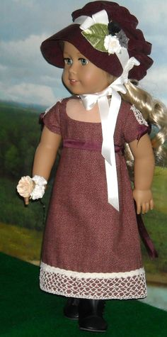 1812 Regency Dress with Burgundy Pelisse and Bonnet via Etsy. The dress is a deep burgundy cotton w/ a low neckline, fully lined bodice. The short sleeves are trimmed w/ wide lace and bows. The same lace is at the base of the skirt which is flat in front, gathered at the back which closes w/ ultra thin velcro. A burgundy ribbon ties about the waist.By SugarloafDollClothes.