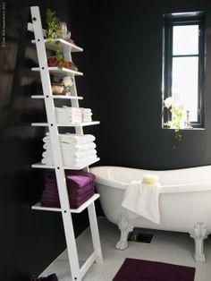 HJÄLMAREN vägghylla håller handdukar och flaskor inom räckhåll från badkaret.