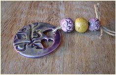 Assembly consisting of a pendant and three ceramic balls. The pendant has a round shape and a beautiful embossed, enamel is purple. Two ball...