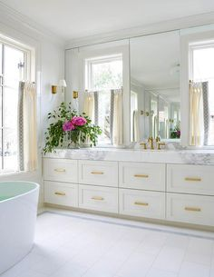 Glam master bathroom boasts a light gray washstand fitted with stacked dresser like drawers adorned with long brass pulls topped with gray and white marble countertop framing a white porcelain sink and antique brass hook and spout faucet.