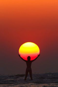 PRAISE THE SUN Photograph by Anton Jankovoy | jankovoy.com In this perfectly timed sunset capture by Anton Jankovoy, we see the silhouette of a woman appearing to hold/praise the sun. The photo was taken in July of 2011 at Paradise Beach in Maharashtra, India. To get the shot Anton used a FL…