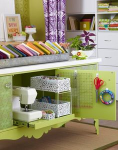 A handy pullout shelf in the lower compartment of a cabinet make a sewing machine and supplies accessible, but out of sight. Stacked white bins and removeable hooks on the back of the cabinet door further maximuze the interior space.