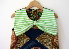 NOUVELLE COLLECTION    Cette robe sans manches africaine mignonne a un collier magnifique grand arc en vert et blanc à rayures cotton.fabric organique. La robe colorée a trois boutons de tissu rayé et deux pressions invisibles comme une fermeture au dos. Cest du genou-longueur et légèrement en forme de A - une sophistiqué et moderne-robe dété pour les petites filles.    La robe de léchantillon est en taille 110.    Petit marin voyages autour du monde, collecte des trésors magnifiques et…