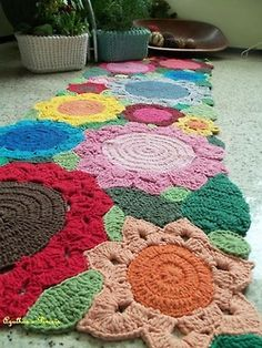 oversized crochet flowers pieced together to form a rug - just for inspiration