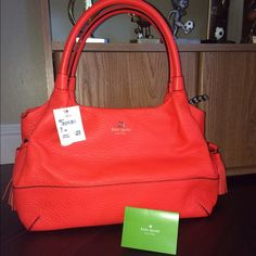 "Kate Spade Stevie Southport Avenue Flame orange New Never used... But have some miner scratches on leather.. Please see last picture..A crisp color, this Kate Spade handbag is very fashionable...Complemented with twill lining and a top zip closure. Kate Spade New York Flame Pebbled Leather with Tassel Drawstring 7"" Drop Double Leather Handles Measures: 13.5"" (W) x 9 (H) x 6"" (D) Zip Top Closure Twill lining with One zip pocket & Two multi-purpose pockets kate spade Bags"