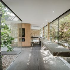 A custom #kitchen with a cantilevered countertop mimics the way the house is perched on a hillside, seeming to defy gravity. #concrete #glass #portuguese