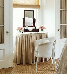 skirted vanity table in front of a window between two closets