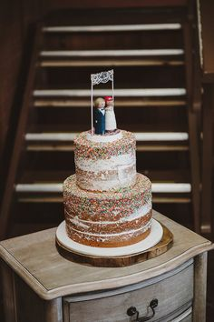 Naked wedding cake with hundreds and thousands rainbow sprinkles and DIY wooden bride and groom topper   Lauren Campbell