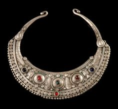 Afghanistan | Silver, disc-shaped flattened, richly decorated with appliqued ornaments and ploychrome glass stones, the janus-headed birds deriving from pre-islamic times, being a popular motif in Afghanistan; such crescent-shaped neckrings are worn by women of various oriental ethnic groups, not only by Paschtunian women | Est 500 - 800 €