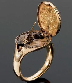 1570: A rare 16th century ring, possibly German. The hinged oval bezel, designed as a seal is engraved with a coat of arms and opens to reveal a sundial & compass.
