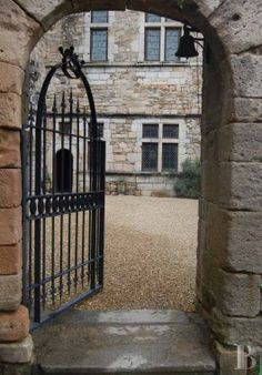 Medieval castle in Longuedoc-Roussillon, France (Provence, region of Cévennes).  View into the courtyard.  Love the iron gate, the windows, beautiful bare stone. The castle was originally built in the 9th century and was expanded in the centuries following.