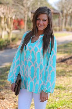 """This soft, billowy blouse is our favorite shade of aqua! The cute pattern and shiny gold buttons give this carefree top wonderful details of elegance! Fits true to size. Miranda is wearing the small.  From the shoulder to the hem: S-24"""", M-25"""", L-26"""", XL-27"""""""