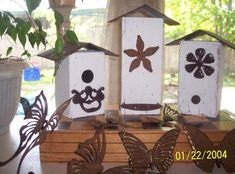 "The birdhouses are just leftover pieces of fence post with some old Home Interiors brass wall hangings with flowers, butterflies and hummingbirds with some of the flowers clipped off. A flattened bottle cap was used on one of the ""bird"" holes and the other is the end from a canned biscuit container. Spray paint them flat black, sprinkle with cinnamon and seal for the rusted look."